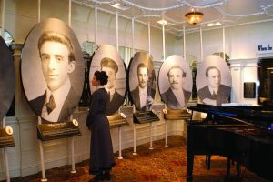 A woman looking at large portraits in a room with a grand piano