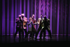 Six men in colorful jackets singing on a stage