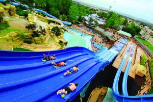Four people sliding down a long multi story water slide